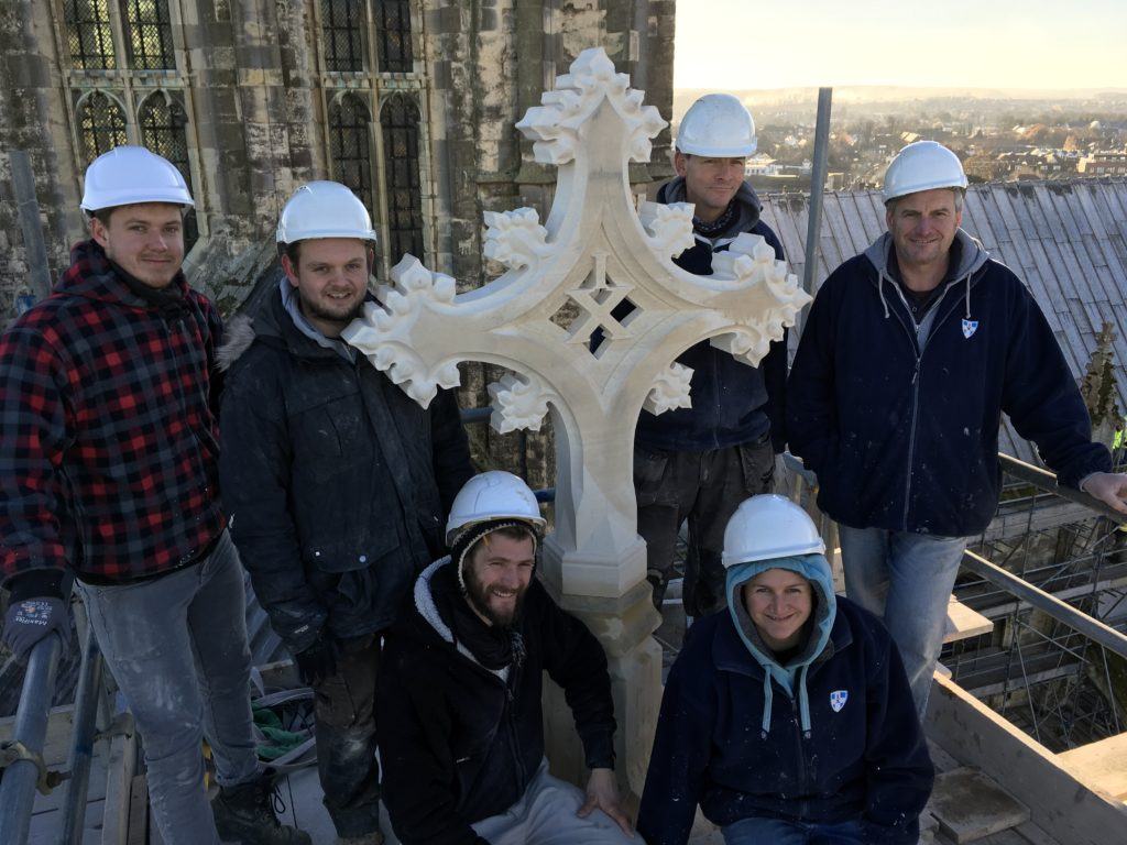 The team of stonemasons pose with the cross