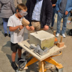 A young lad tries his hand at masonry