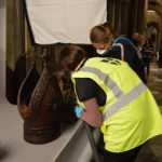 Two of our conservators carefully clean sections from Archbishops Tenison's wooden throne.