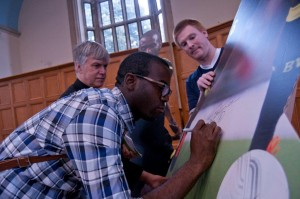 Fabrice Muamba signs his life size photo with the Venerable Stephen Taylor, Archdeacon of Ashford looking on and Mark Binns Canterbury Diocese's IT Manager