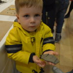 A happy young visitor shows off his clay fish.