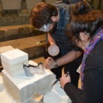 Local university students learn some masonry skills.